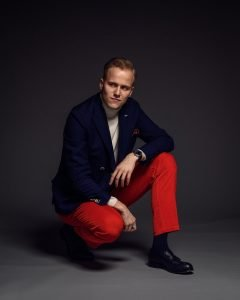 Red and Navy blue men's outfit: classic color combination with red corduroy trousers, navy double breasted blazer, cream turtleneck and navy tassel loafers