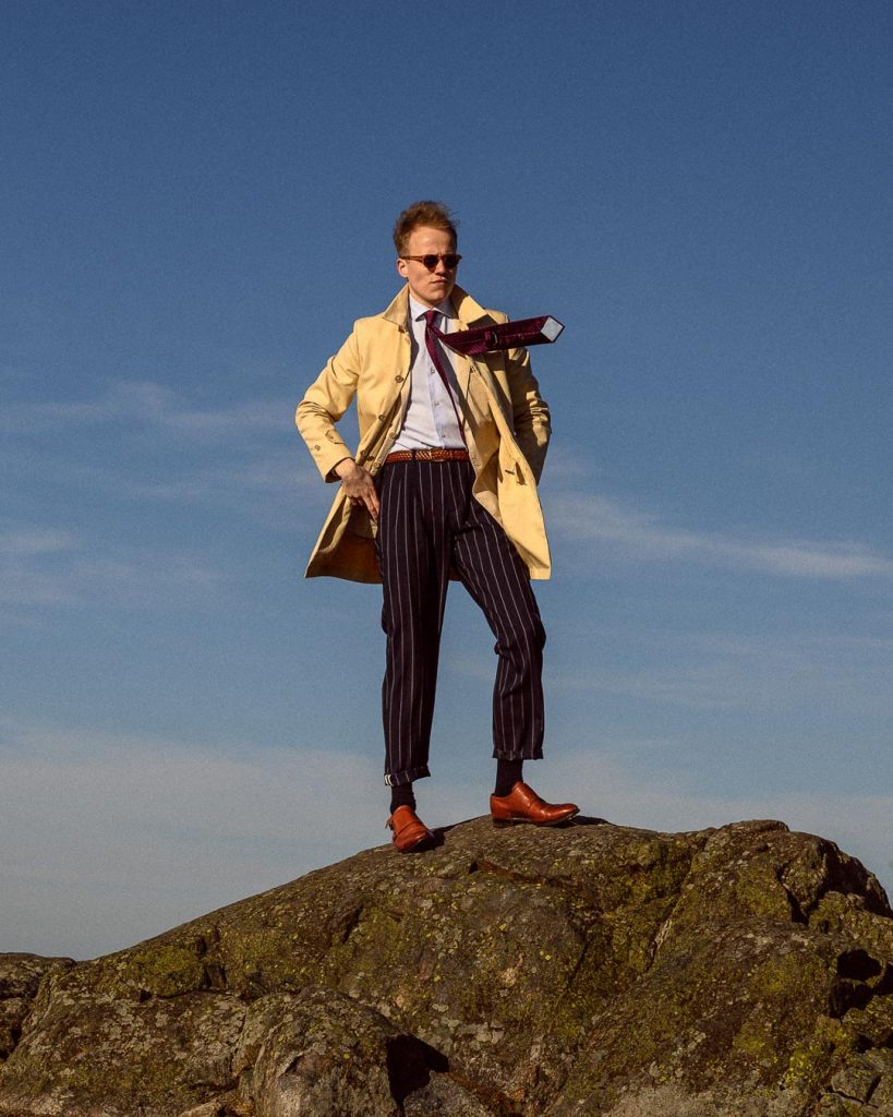 Early-Spring style for men: Trench coat, striped tie, striped trousers, light blue shirt, sunglasses, brown double monk strap shoes